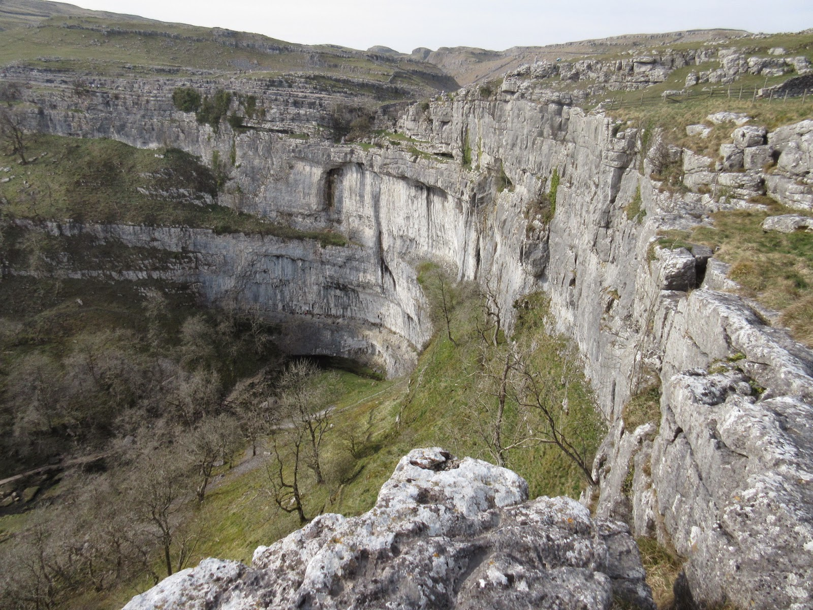 Malham Cove, where the cliff has been been cut back 500 metres from the fault line – the horse shoe shape resulting from less erosion at the sides than at the centre. Stephen Oldfield