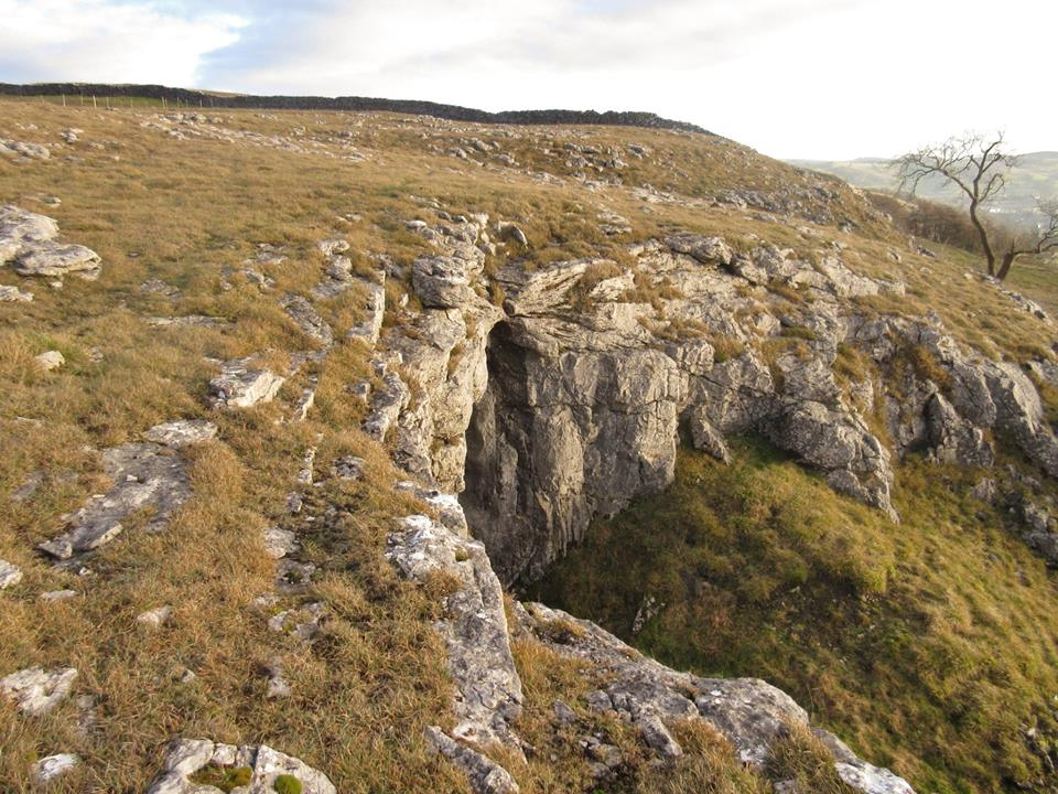 Remnants of an ancient landscape: Gully Cave with its obvious former cascade and the impressive entrance to Kinsey Cave (below) a former phreatic resurgence. Stephen Oldfield