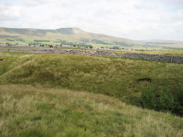 The grassy saddle of the massive rock bridge spanning the hole, with the Mere 15 metres below moor level. Stephen Oldfield