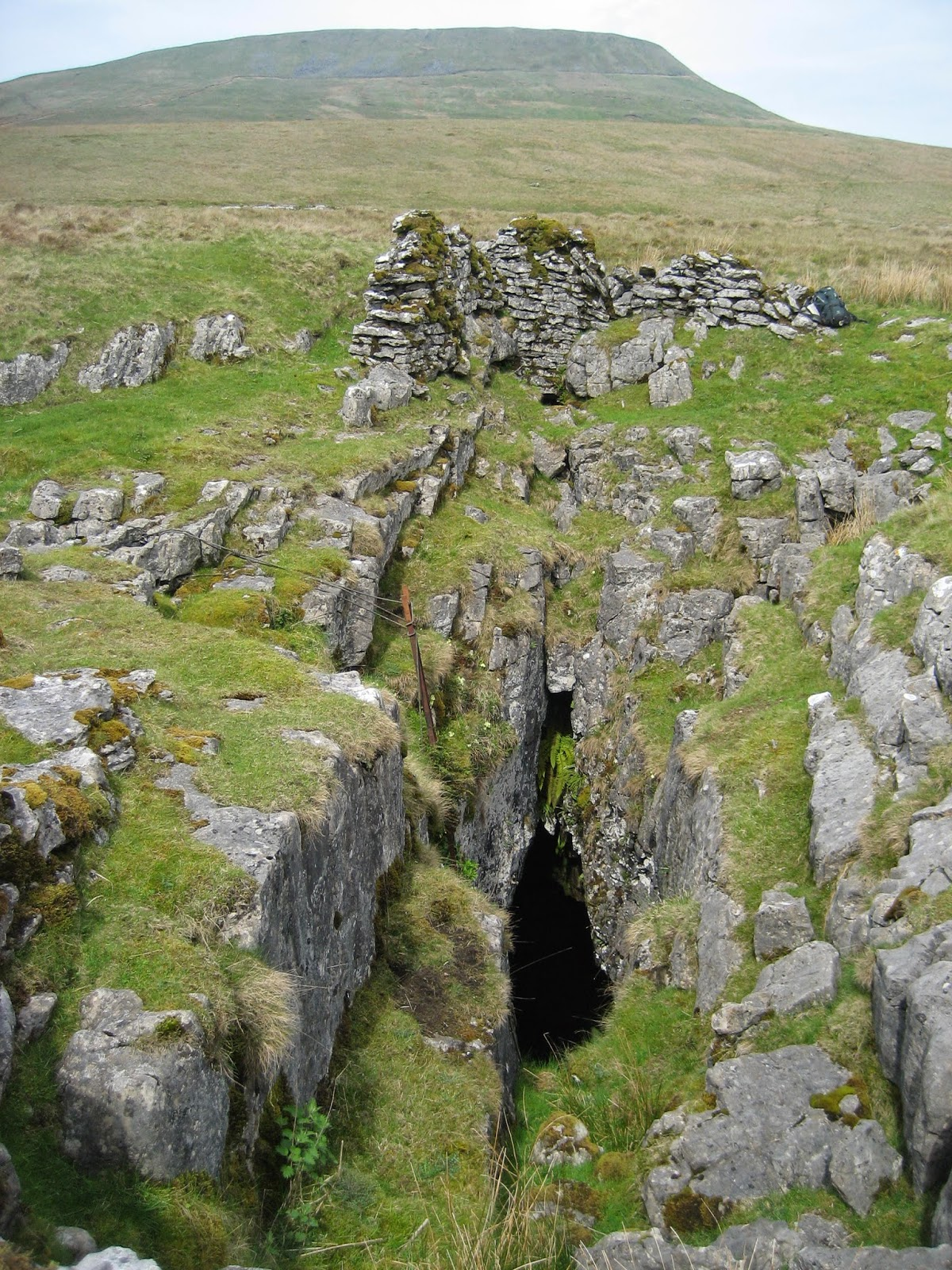 Sulber Pot, looking west towards Simon Fell, lying directly on the line of the Sulber Nick Fault.  Remains of an old encircling wall can be seen at top centre. Stephen Oldfield
