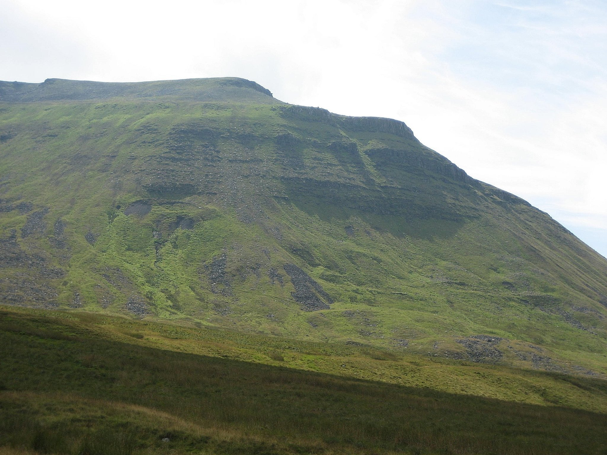 The great pyramid of Ingleborough made up of the Yoredale Series, formed by fluctuating sea levels.  At top left is the main gritstone cap, with the first buttress below it being of the Main Limestone – the highest limestone on the mountain.  Just below, a sandstone buttress looks over the Black Shiver landslip. Stephen Oldfield